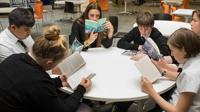 high school pupils reading in school library