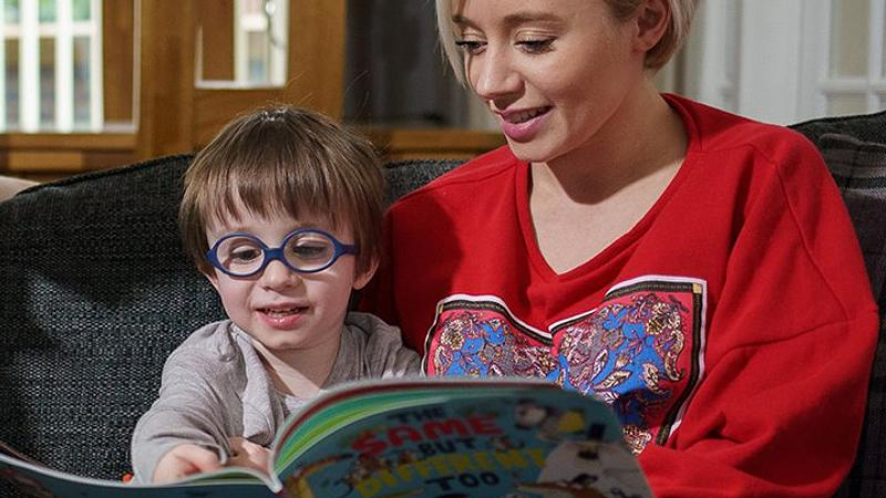 Woman and toddler reading a book together