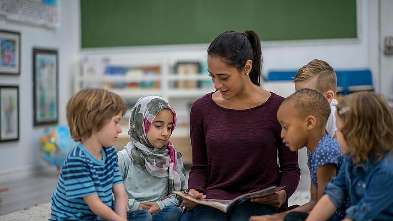 Woman reading a book to a group of children