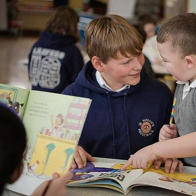 two boys reading a book together in school
