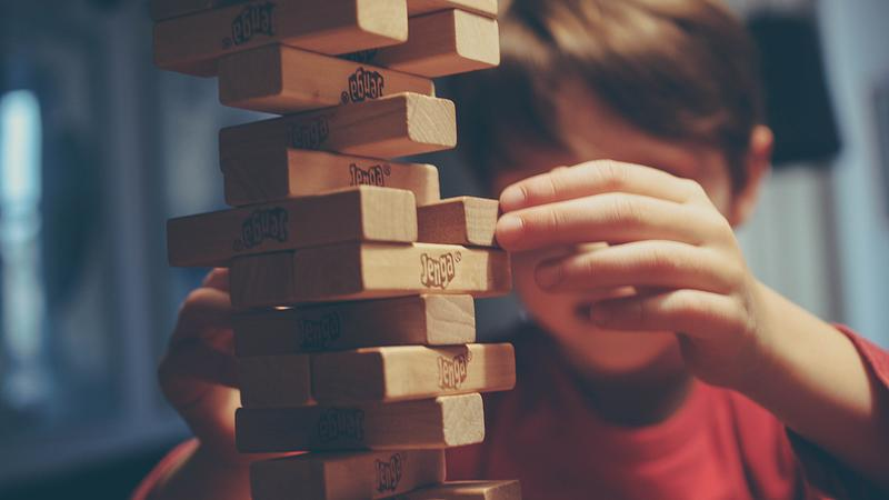 boy playing Book Jenga
