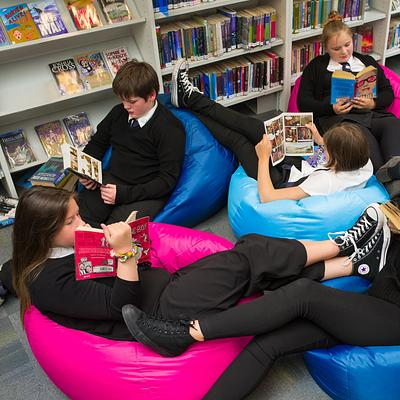 high school pupils reading on bean bags in school library