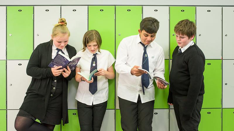 high school pupils reading beside lockers