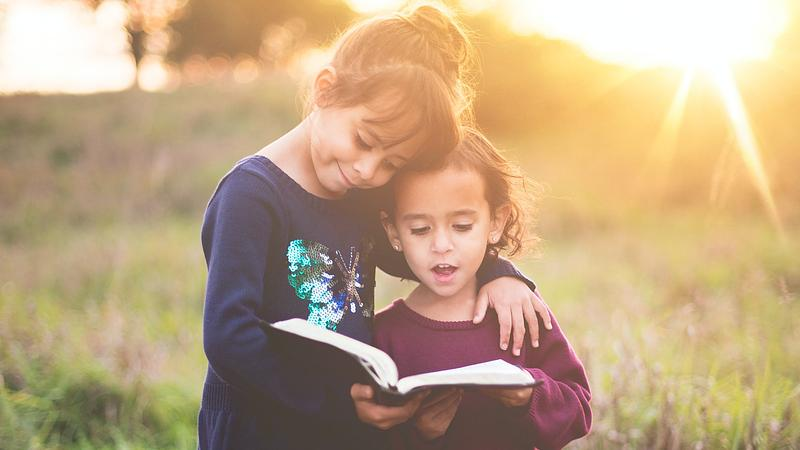 two girls reading a book together outdoors